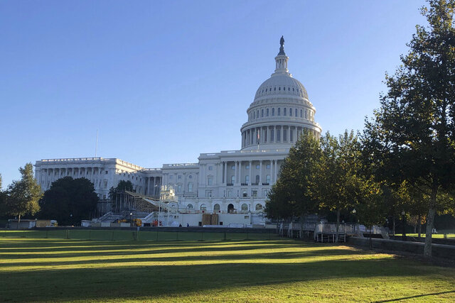Sunlight shines on the lawn in front of the Capitol as workers build the stage, bleachers and tower for TV cameras for the presidential inaugural Saturday, Nov. 7, 2020, in Washington. In the midst of a pandemic and at the end of a hotly contested election campaign, the work goes on. (AP Photo/Mark Sherman)