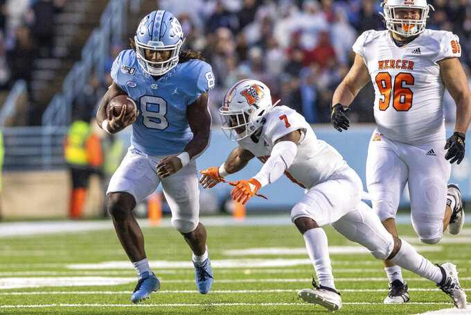 North Carolina's Michael Carter (8) carries the ball as Mercer's Eric Jackson (7) attempts a tackle during an NCAA college football game in Chapel Hill, N.C., Saturday, Nov. 23, 2019. (AP Photo/Ben McKeown)