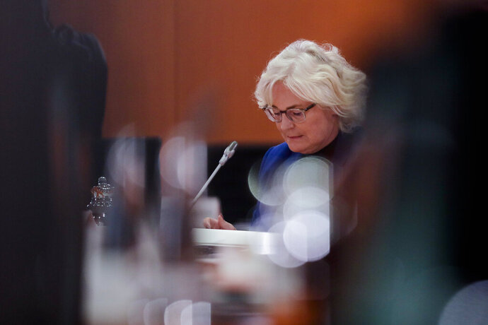 German Justice Minister Christine Lambrecht reads in her documents prior to the weekly cabinet meeting of the German government at the chancellery in Berlin, Wednesday, Oct. 21, 2020. (AP Photo/Markus Schreiber, Pool)
