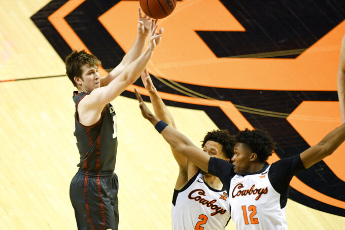 Oklahoma guard Alondes Williams (15) shoots while under pressure from Oklahoma State guard Cade Cunningham (2) and forward Matthew-Alexander Moncrieffe (12) during an NCAA college basketball game Monday, March 1, 2021, in Stillwater, Okla. (AP Photo/Brody Schmidt)