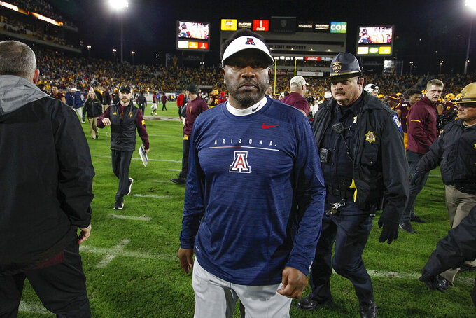 FILE- In this Nov. 30, 2019, file photo, Arizona coach Kevin Sumlin walks off the field after his team's 24-14 loss to Arizona State in an NCAA college football game, Saturday,, in Tempe, Ariz. Sumlin was fired Saturday, Dec. 12, 2020, less than 24 hours after a 70-7 loss to Arizona State that stretched the Wildcats' losing streak to 12 games spanning two seasons.  (AP Photo/Darryl Webb, File)
