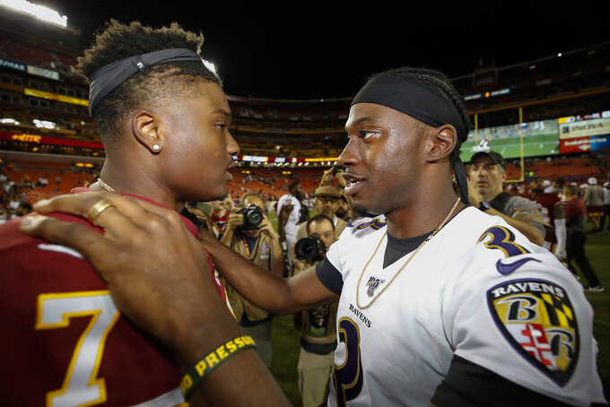 Washington Redskins quarterback Dwayne Haskins (7) and Baltimore Ravens quarterback Robert Griffin III (3) talk after an NFL preseason football game Thursday, Aug. 29, 2019, in Landover, Md. (AP Photo/Alex Brandon)