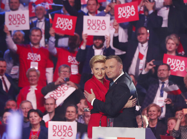 Poland's President Andrzej Duda is hugging First Lady Agata Kornhauser-Duda during a ruling Law and Justice party convention that backed his re-election bid in the May 10 presidential vote in Warsaw, Poland, Saturday, Feb. 15, 2020. (AP Photo/Czarek Sokolowski)