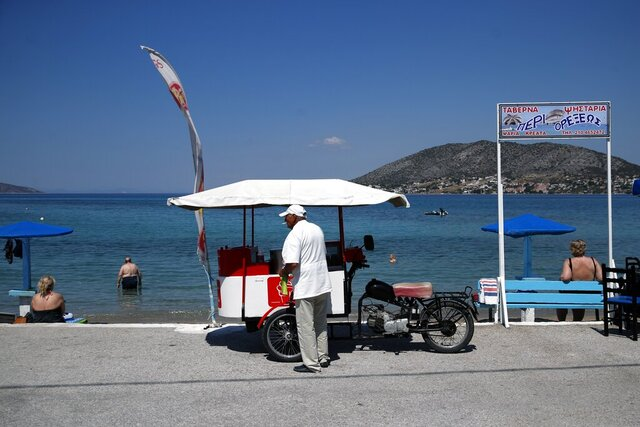 A motorbike ice-cream vendor smokes a cigarette as he waits for customers next to a beach on Salamina island, west of Athens, Monday, June 29, 2020. (AP Photo/Thanassis Stavrakis)