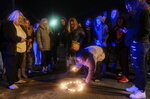 In this Monday, Jan. 13, 2020 photo, Ravin Pinkelton arranges candles in the shape of a heart as law enforcement officers investigate a vacant house in Port Clinton, Ohio., where the body of Harley Dilly, 14, was found inside the chimney. The teen had been missing for more than three weeks. (Jeremy Wadsworth/The Blade via AP)