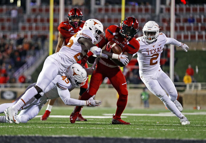 Texas Tech's Da'Leon Ward (21) is tackled by Texas' B.J. Foster (25) and Anthony Wheeler (45) during the second half of an NCAA college football game Saturday, Nov. 10, 2018, in Lubbock, Texas. (AP Photo/Brad Tollefson)