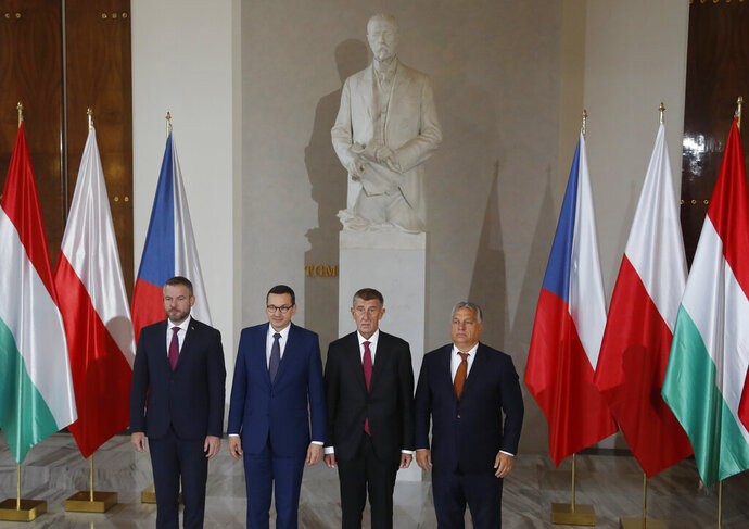 Prime Ministers of Slovakia Peter Pellegrini, left, Poland Mateusz Morawiecki, 2nd left, Czech Republic Andrej Babis, 2nd right, and Hungary Viktor Orban, right, pose for a photo during the V4 summit at the Prague Castle, Czech Republic, Thursday, Sept. 12, 2019. Statue of first President of Czechoslovakia Tomas Garrigue Masaryk is in the background. (AP Photo/Petr David Josek)