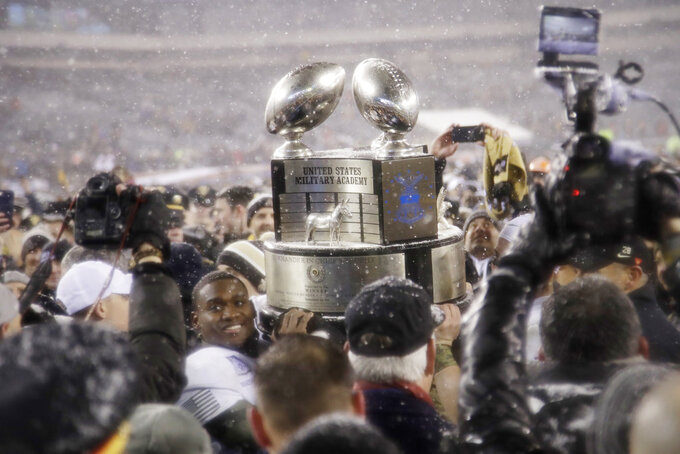 FILE- In this Dec. 9, 2017, file photo, Army's Ahmad Bradshaw holds up the Commander-in-Chief's Trophy after Army defeated Navy in an NCAA college football game in Philadelphia. It's been a year since Air Force lost the Commander-in-Chief's Trophy, and the Falcons want it back. Air Force has won the coveted hardware, which goes to the champion of the annual series among the three service academies, a record 20 times. (AP Photo/Matt Rourke, File)