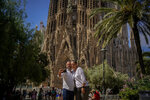 """A couple pose for a picture in front of Sagrada Familia Basilica designed by architect Antoni Gaudi in Barcelona, Spain, Friday, July 9, 2021. Spain's top diplomat is pushing back against French cautions over vacationing on the Iberian peninsula. Southern Europe's holiday hotspots worry that repeated changes to rules on who can visit is putting people off travel. On Thursday, France's secretary of state for European affairs, Clement Beaune, advised people to """"avoid Spain and Portugal as destinations"""" when booking their holidays because COVID-19 infections are surging there. (AP Photo/Joan Mateu)"""