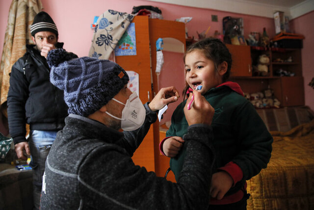 A little girl gets help from Valeriu Nicolae to learn brushing his teeth correctly as her father watches n Nucsoara, Romania, Saturday, Jan. 9, 2021. The rights activist has earned praise for his tireless campaign to change for the better the lives of the Balkan country's poorest and underprivileged residents, particularly the children. (AP Photo/Vadim Ghirda)