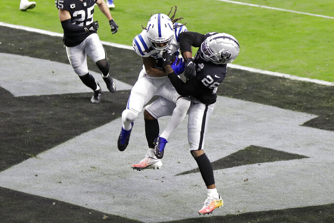 Indianapolis Colts wide receiver T.Y. Hilton (13) catches a touchdown pass over Las Vegas Raiders cornerback Nevin Lawson (26) during the first half of an NFL football game, Sunday, Dec. 13, 2020, in Las Vegas. (AP Photo/Isaac Brekken)