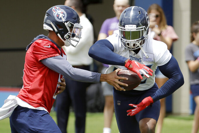 Tennessee Titans quarterback Marcus Mariota hands off to running back Derrick Henry during an organized team activity at the Titans' NFL football training facility Tuesday, June 11, 2019, in Nashville, Tenn. Both players are in the final year of their contract. (AP Photo/Mark Humphrey)