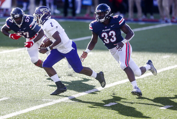 Western Carolina quarterback Mark Wright (2) carries the ball as he is defended by Liberty defensive end Stephen Sings V (33) during the second half of an NCAA football game Saturday, Nov. 14, 2020, in Lynchburg, Va. (AP Photo/Shaban Athuman)