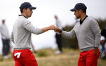 U.S. team player Xander Schauffele, left, fist bumps with playing partner Patrick Cantlay in their foursome match during the President's Cup golf tournament at Royal Melbourne Golf Club in Melbourne, Saturday, Dec. 14, 2019. (AP Photo/Andy Brownbill)