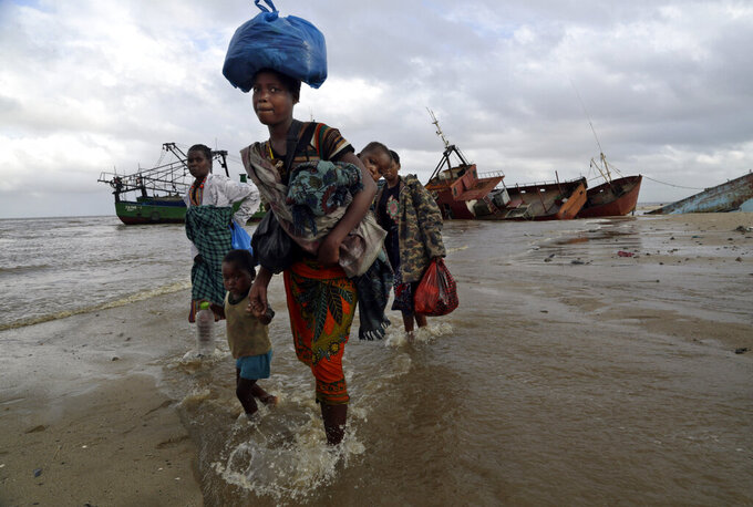 FILE — In this Saturday, March 23, 2019 file photo, displaced families arrive after being rescued by boat from a flooded area of Buzi district, 200 kilometers (120 miles) outside Beira, Mozambique. The U.N. high commissioner for refugees, Filippo Grandi said Friday June 17, 2021, that conflicts and the impact of climate change in places like Mozambique were among the leading sources of new flows of refugees and internally displaced people in 2020. (AP Photo/Tsvangirayi Mukwazhi, File)