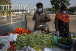 An Indian couple wearing face masks as a precautionary measure against the coronavirus sells vegetables by a roadside in Kochi, Kerala state, India, Friday, Nov. 20, 2020. India's total number of coronavirus cases since the pandemic began crossed 9 million on Friday. (AP Photo/R S Iyer)