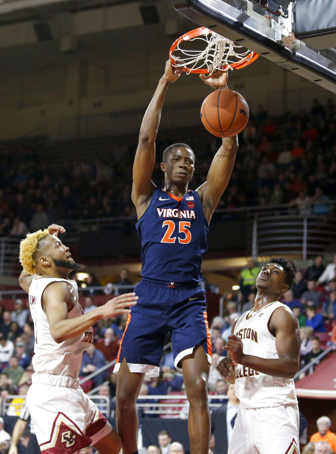 Virginia forward Mamadi Diakite (25) dunks as Boston College guard Ky Bowman, left, and forward Jairus Hamilton, right, watch during the first half of an NCAA basketball game Wednesday, Jan. 9, 2019, in Boston. (AP Photo/Mary Schwalm)