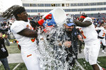 North coach Matt Patricia of the Detroit Lions is dunked by North edge rusher Trevon Hill of Miami (95) and North defensive lineman McTelvin Agim of Arkansas (91) after they defeated the South team 34-17 in the Senior Bowl college football game Saturday, Jan. 25, 2020, in Mobile, Ala. (AP Photo/Butch Dill)