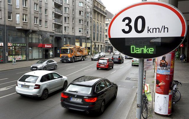 FILE - In this Monday, May 20, 2019 file photo, cars pas by a speed limit traffic sign at the 'Leipziger Strasse' in Berlin, Germany. Campaigners in Berlin are launching a drive to collect signatures for a vote on making the heart of the German capital largely car free. Backers of the plan said Wednesday, Oct. 21, 2020 that banning most cars from the city center would improve quality of life, improve road safety and help Germany achieve its climate goals. (AP Photo/Michael Sohn, file)