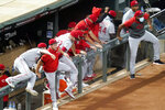 Cincinnati Reds players climb over the dugout fence and head to celebrate with pitcher Wade Miley after the Reds earned a playoff berth with a 7-2 over the Minnesota Twins in a baseball game Friday, Sept. 25, 2020, in Minneapolis. (AP Photo/Jim Mone)