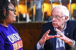 Artinese Malachi, of Swissvale, Pa. and SEIU union LPN, left, listens as U.S. Sen. Bernie Sanders, Democratic presidential candidate speaks during a roundtable discussion with UPMC Hospitals and SEIU healthcare workers prior to his attendance at the presidential candidate Public Education Forum, Saturday, Dec. 14, 2019, on Locust Street in Uptown. (Pittsburgh Post-Gazette via AP)