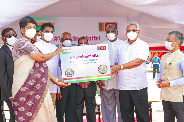 Sri Lankan President Gotabaya Rajapaksa, second right, receives a box of COVID-19 vaccines upon arrival from India, in Colombo, Sri Lanka, Thursday, Jan. 28, 2021. Rajapaksa on Thursday welcomed the first 500,000 doses of a COVID-19 vaccine from India, which has donated the shots to eight countries in the region. (Sri Lankan Presidents Office via AP)
