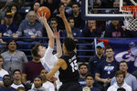 San Diego guard Finn Sullivan, left, shoots as Gonzaga forward Brandon Clarke defends during the first half of an NCAA college basketball game Saturday, Feb. 16, 2019, in San Diego. (AP Photo/Gregory Bull)