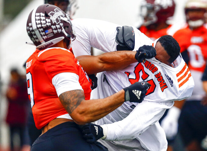 South offensive tackle Tytus Howard of Alabama State (58) loses his helmet in a drill with South defensive end Montez Sweat of Mississippi State (9) during practice for Saturday's Senior Bowl college football game, Tuesday, Jan. 22, 2019, in Mobile, Ala. (AP Photo/Butch Dill)