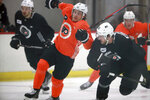 Philadelphia Flyers forward Travis Konecny, left foreground, tries to skate around teammate Tyler Wotherspoon, right, during an NHL hockey practice in Voorhees, N.J., Tuesday, Jan. 5, 2021.  ( (David Maialetti/The Philadelphia Inquirer via AP)