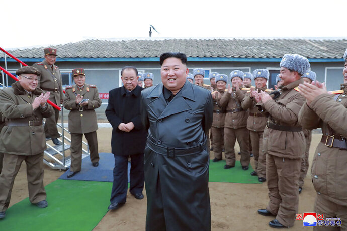 FILE - This undated file photo provided on Friday, Nov. 29, 2019, by the North Korean government, shows North Korean leader Kim Jong Un, center, surrounded by a military unit, reacts to what it claims as a test firing of its