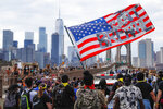 FILE - In this June 4, 2020, file photo protesters march on the Brooklyn Bridge after a rally in Cadman Plaza Park in New York. Protests continued following the death of George Floyd, who died after being restrained by Minneapolis police officers on May 25. The three month stretch between the symbolic kickoff and close of America's summer has both galvanized broad public support for the racial justice movement and exposed the obstacles to turning that support into concrete political and policy changes. (AP Photo/John Minchillo, File)