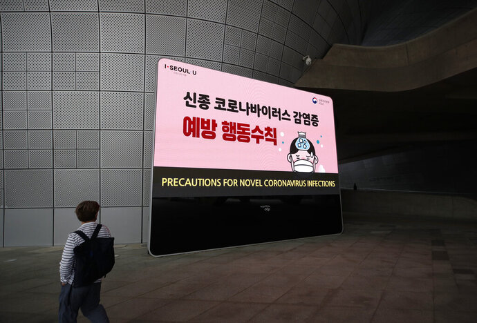 A man wearing a face mask walks by a screen showing precautions against the new coronavirus in Seoul, South Korea, Tuesday, May 12, 2020. (AP Photo/Lee Jin-man)