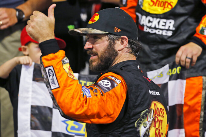 Martin Truex Jr. (19) celebrates his win in the NASCAR Cup Series auto race at Richmond Raceway in Richmond, Va., Saturday, Sept. 21, 2019. (AP Photo/Steve Helber)