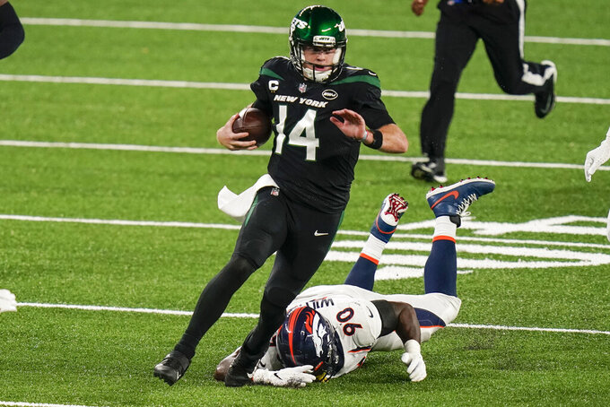 New York Jets quarterback Sam Darnold (14) gets past Denver Broncos' DeShawn Williams while rushing for a touchdown during the first half of an NFL football game Thursday, Oct. 1, 2020, in East Rutherford, N.J. (AP Photo/Seth Wenig)