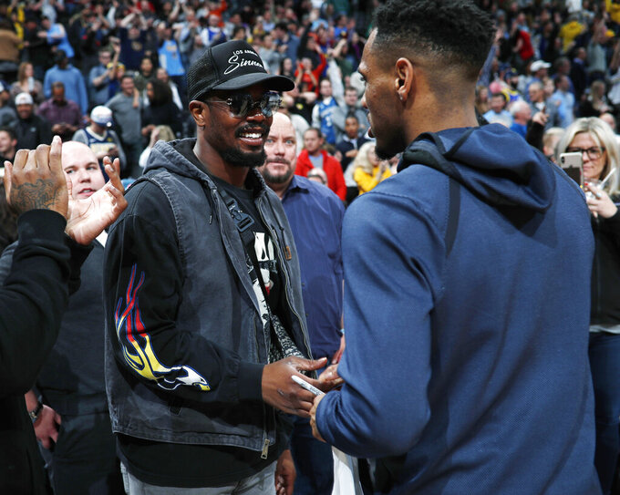 Denver Broncos linebacker Von Miller, left, shakes hands with Denver Nuggets guard Monte Morris after Morris gave his jersey to Miller following the team's NBA basketball game against the Minnesota Timberwolves on Wednesday, April 10, 2019, in Denver. The Nuggets won 99-95. (AP Photo/David Zalubowski)