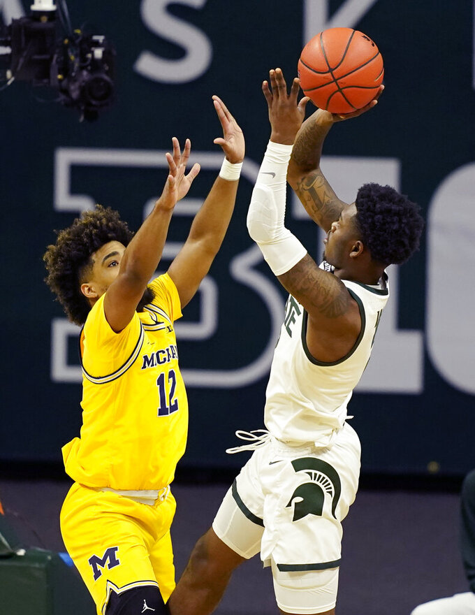 Michigan State guard Rocket Watts (2) shoots over Michigan guard Mike Smith (12) during the first half of an NCAA college basketball game, Sunday, March 7, 2021, in East Lansing, Mich. (AP Photo/Carlos Osorio)