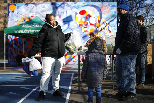 A family gathers pre-bagged food donations at City Harvest's Bed-Stuy Mobile Market operating in the Tomkins Houses area, Wednesday, March 18, 2020, in New York. Mayor Bill de Blasio said New York City residents should be prepared for the possibility of a
