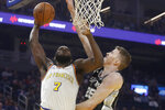 Golden State Warriors forward Eric Paschall (7) shoots next to San Antonio Spurs center Jakob Poeltl (25) during the first half of an NBA basketball game in San Francisco, Friday, Nov. 1, 2019. (AP Photo/Jeff Chiu)