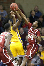 Oklahoma's Jamal Bieniemy (24) blocks a shot attempt by Minnesota's Marcus Carr (5) during the first half of an NCAA college basketball game in Sioux Falls, S.D., Saturday, Nov. 9, 2019. (AP Photo/Nati Harnik)