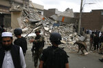 Pakistani security forces demolish the hideout of militants in Peshawar, Pakistan, Tuesday, April 16, 2019. Pakistani authorities say a raid by security forces on a militant hideout in the northwestern city of Peshawar triggered a 15-hour shootout in which a police officer and many suspected militants were killed. (AP Photo/Muhammad Sajjad)
