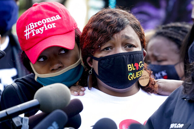 Tamika Palmer, the mother of Breonna Taylor, right, listens to a news conference, Friday, Sept. 25, 2020, in Louisville, Ky. Family attorney Ben Crump is calling for the Kentucky attorney general to release the transcripts from the grand jury that decided not to charge any of the officers involved in the Black woman's death. (AP Photo/Darron Cummings)