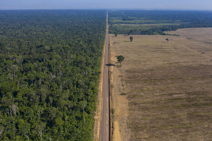 FILE - In this Nov. 25, 2019 file photo, highway BR-163 stretches between the Tapajos National Forest, left, and a soy field in Belterra, Para state, Brazil. Preliminary data released on June 4, 2021, signaled deforestation of Brazil's Amazon in May 2021 extended this year's surge compared to 2020. (AP Photo/Leo Correa, File)
