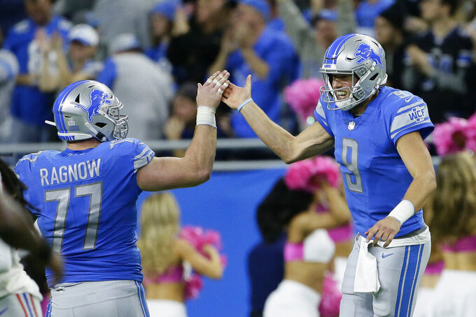 Detroit Lions quarterback Matthew Stafford (9) and center Frank Ragnow (77) celebrate after a play during the second half of an NFL football game against the New York Giants, Sunday, Oct. 27, 2019, in Detroit. (AP Photo/Duane Burleson)