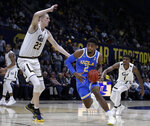 UCLA's Cody Riley, center, drives the ball between California's Connor Vanover (23) and Darius McNeill (1) during the first half of an NCAA college basketball game Wednesday, Feb. 13, 2019, in Berkeley, Calif. (AP Photo/Ben Margot)