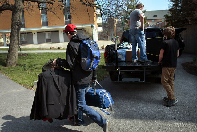 A Washington University engineering student, who declined identification, removes his belongings from his dormitory at the school in St. Louis on Wednesday, March 11, 2020, to move back home to Ballwin, Mo. A few other students on the South Danforth campus were doing the same as dorms were set to shutter Sunday from fear of the coronavirus. Students on spring break were told not to return to campus and to continue their classes online. (Robert Cohen/St. Louis Post-Dispatch via AP)