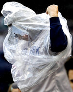 A fan tries to stay dry during the second inning of a baseball game between the New York Yankees and the Chicago White Sox in Chicago, Saturday, June 15, 2019. (AP Photo/Nam Y. Huh)