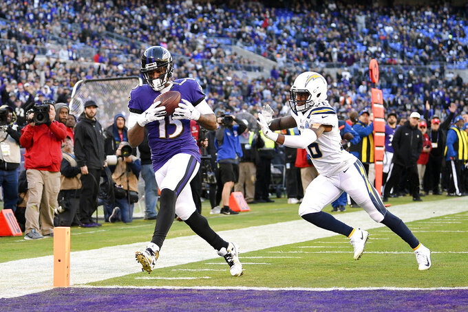 Baltimore Ravens wide receiver Michael Crabtree, left, scores a touchdown in front of Los Angeles Chargers cornerback Casey Hayward in the second half of an NFL wild card playoff football game, Sunday, Jan. 6, 2019, in Baltimore. (AP Photo/Nick Wass)