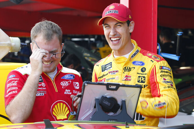 Joey Logano, right, shares a laugh with a crew member in the garage at Martinsville Speedway In Martinsville, Va., Saturday, Oct. 26, 2019. Elliott had an engine failure less than five minutes into the opening practice for the third round of NASCAR's playoffs. (AP Photo/Steve Helber)