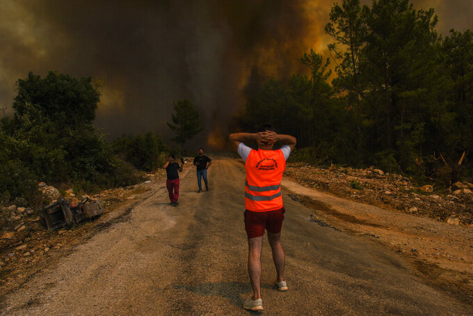FILE  - In this Sunday, Aug. 1, 2021 file photo, people run away from the fire-devastated Sirtkoy village, near Manavgat, Antalya, Turkey. Scientists say there's something different this year from the recent drumbeat of climate weirdness. This summer a lot of the places hit by weather disasters are not used to getting extremes and many of them are wealthier, which is different from the normal climate change victims. That includes unprecedented deadly flooding in Germany and Belgium, 116-degree heat records in Portland, Oregon and similar blistering temperatures in Canada, along with wildfires. Now Southern Europe is seeing scorching temperatures and out-of-control blazes too. And the summer of extremes is only getting started. Peak Atlantic hurricane and wildfire seasons in the United States are knocking at the door. (AP Photo, File)