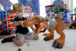 """In this Aug. 30, 2018, photo Alexander, 5, explores a Jurassic World Jurassic Rex at the Walmart Toy Shop event in New York. Walmart says 30 percent of its holiday toy assortment will be new. It will also offer 40 percent more toys on Walmart.com from a year ago. In November and December, the company's toy area will be rebranded as """"America's Best Toy Shop."""" (AP Photo/Richard Drew)"""